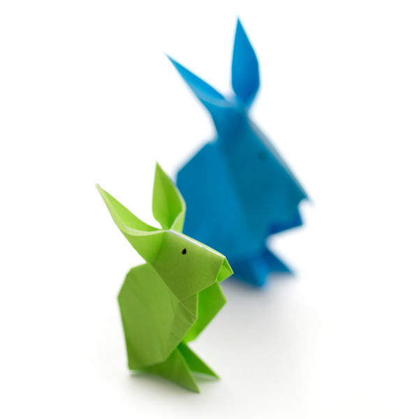A green a d blue rabbit standing side by side